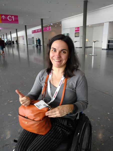 Zufriedene Teilnehmerin mit Teilnahmeausweis und Rollstuhl