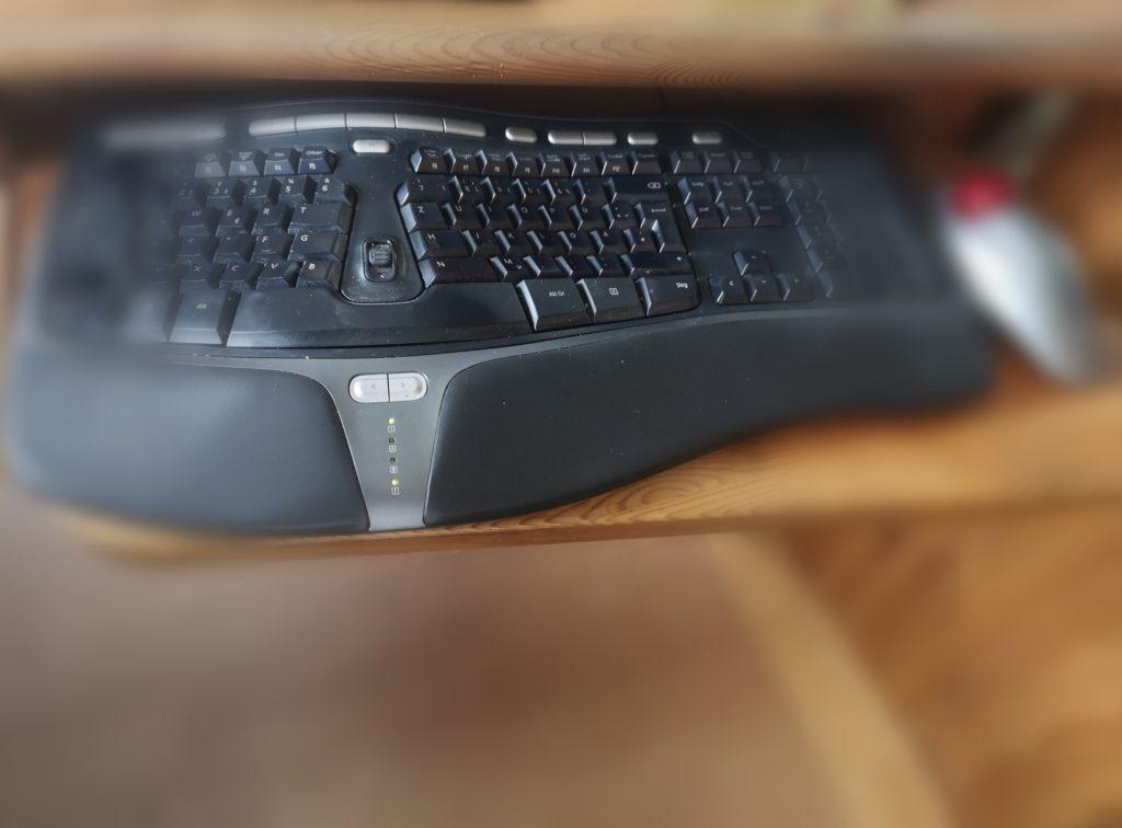 Ergonomische Tastatur und Maus auf Tastaturauszug für mehr Ergonomie am Arbeitsplatz