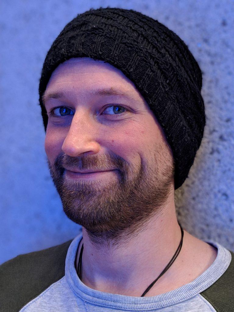 Daniel Landes, lächelnder Mann mit schwarzer Mütze und Bart