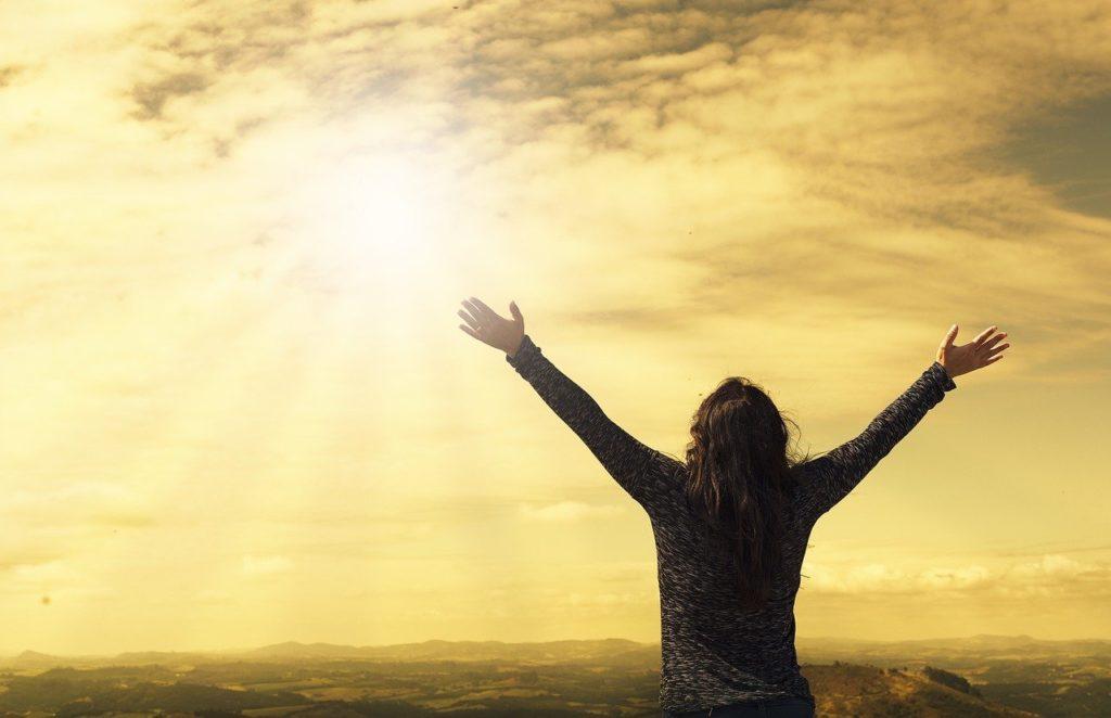 Frau von hinten, reckt sich mit ausgebreiteten Armen der Sonne entgegen