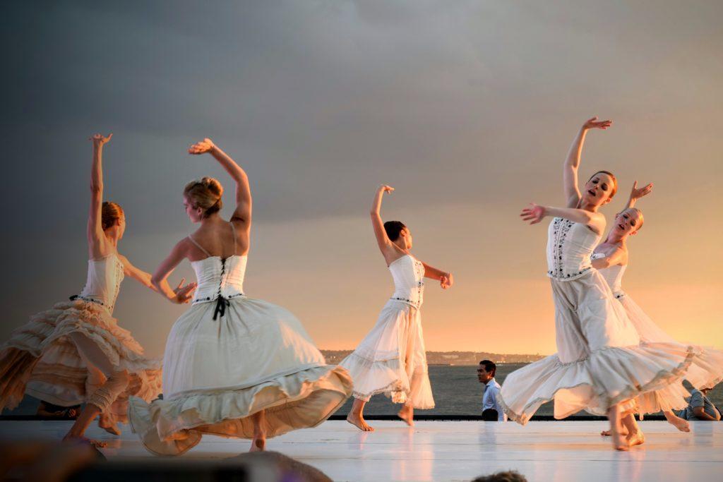 Fünf Tänzerinnen in weißen Kostümen bei einer Ballett-Aufführung im Freien.